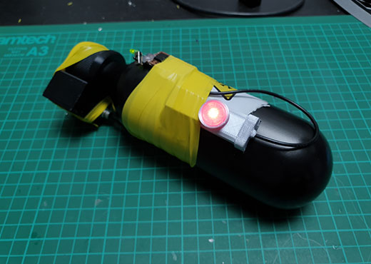 Smoke gas canister cosplay prop from Six Siege with red LED on a cutting mat